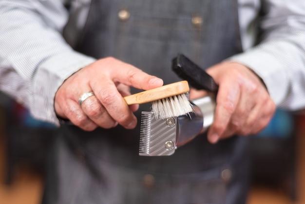 Friseur, der elektrischen haarschneider säubert.