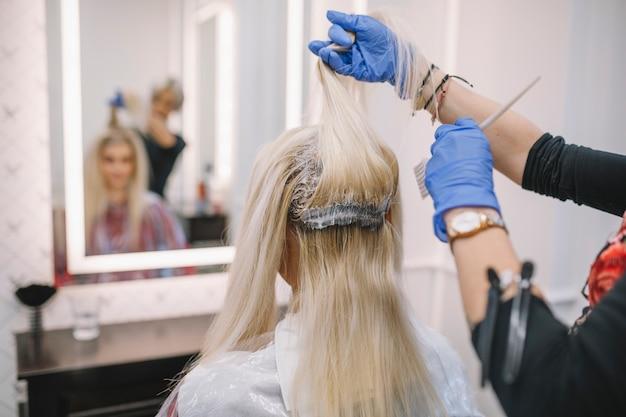 Friseur, der farbe mit bürste ausbreitet