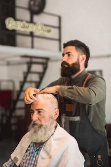 Friseur, der frisur korrigiert, um kunden zu bemannen