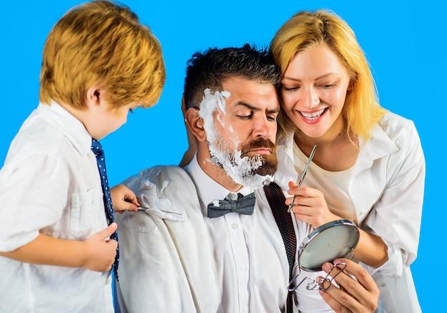 Friseur, der frisur macht. familientag. mutter, die dem vater und dem kleinen sohn haare schneidet, die vaterbart mit rasiermesser rasieren.
