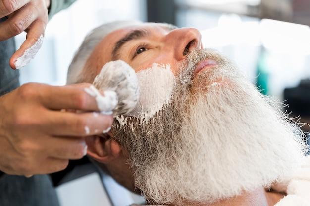 Friseur, der für das rasieren des älteren kunden sich vorbereitet