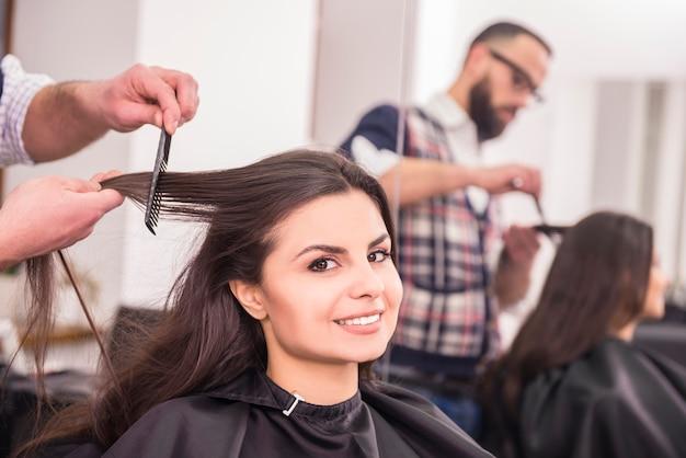 Friseur, der haar des weiblichen kunden kämmt.