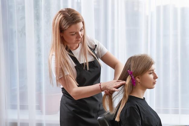 Friseur, der haare eines kunden in einem schönheitssalon stylt
