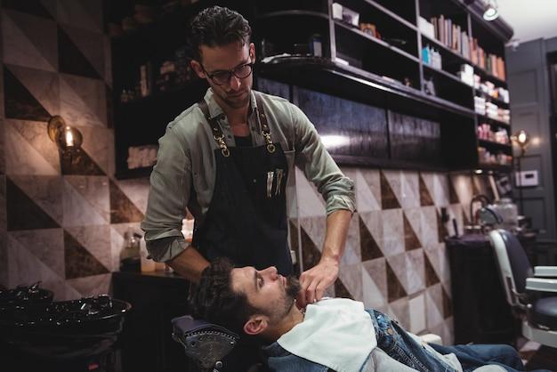Friseur, der handtuch über kundenhals legt