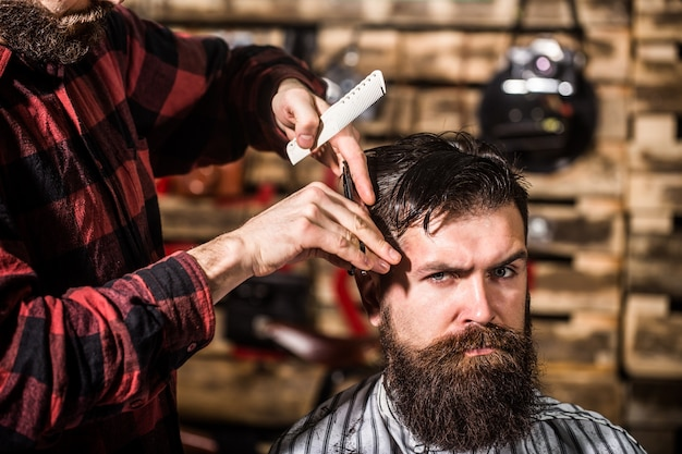 Friseur, der kunden im friseursalon bedient