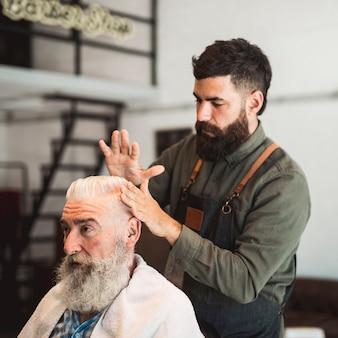 Friseur, der kundenhaar für haarschnitt vorbereitet