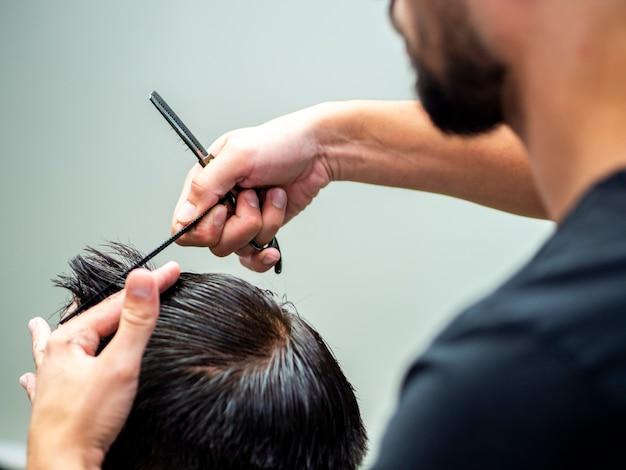 Friseur, der kundenhaarlänge misst