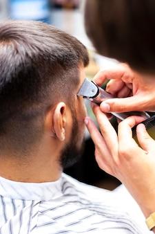 Friseur, der kundenkoteletten trimmt