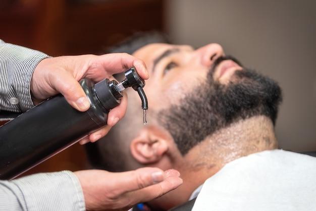 Friseur, der lotion am friseursalon nach dem rasieren zutrifft.