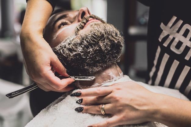 Friseur, der mann im shop rasiert