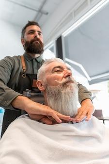 Friseur, der mit gealtertem kunden im salon arbeitet