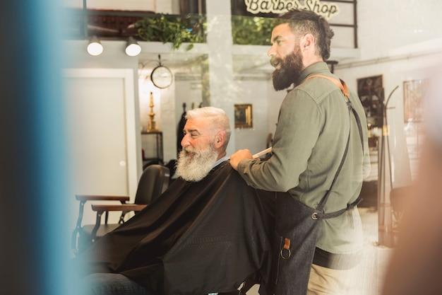 Friseur, der mit gealtertem kunden im studio sich verständigt