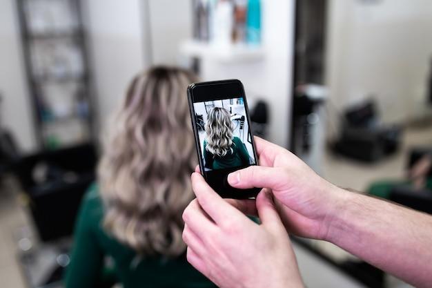 Friseur, der nach dem sterben der haare ein foto von der frisur der reifen frau macht und highlights im friseursalon macht.