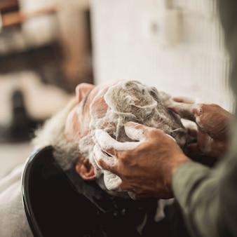 Friseur, der shampoo in kundenhaar massiert