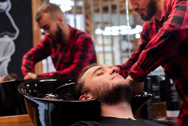 Friseur, der sorgfältig kundenkopf wäscht
