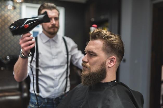 Friseur, der trockner auf haar des kunden verwendet