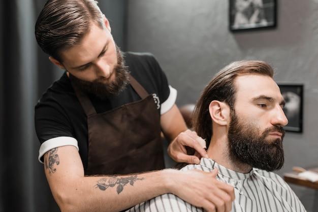 Friseur, der umhang auf männlichen kunden im friseursalon setzt