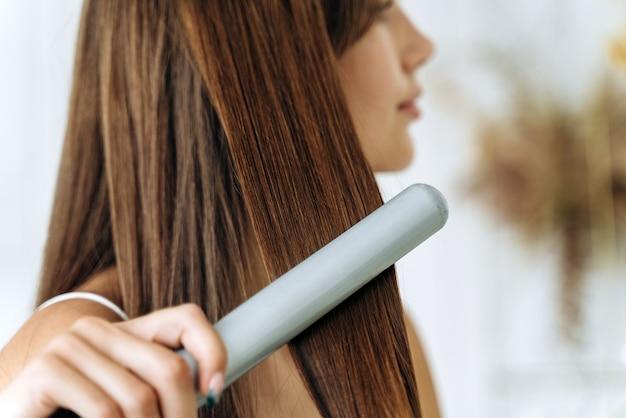 Friseur. frau mit schönen langen glatten haaren mit haarglätter. wunderschönes mädchen, das gesundes haar mit flacheisen glättet. haarbügel- und frisurenkonzept