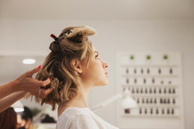 Friseur frisiert süße hübsche junge frau im schönheitssalon. der kundenservice im innenraum schafft ein erstaunliches bild. assistent zum erstellen von frisuren. konzeptstil, zufriedenheit. platz kopieren