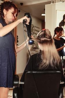 Friseur frisiert süße junge frau im schönheitssalon. der kundenservice im innenraum schafft ein erstaunliches bild. assistent zum erstellen von frisuren. konzept des gesunden lebensstils und des wellness