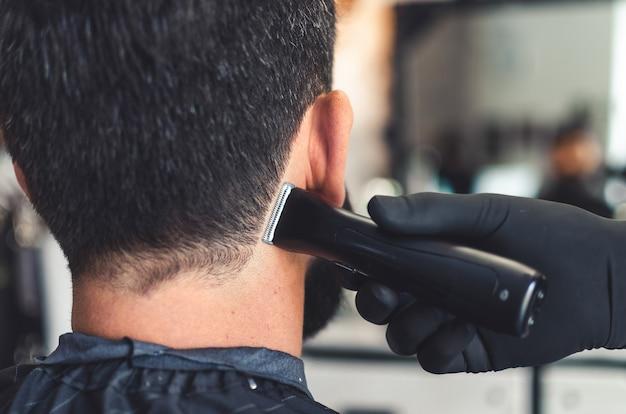 Friseur geschnittene haare am hals und nacken des mannes im friseursalon mit professionellem haarschneidewerkzeug. elektrische trimmermaschine, die haare auf kundenhaut schneidet. nahansicht