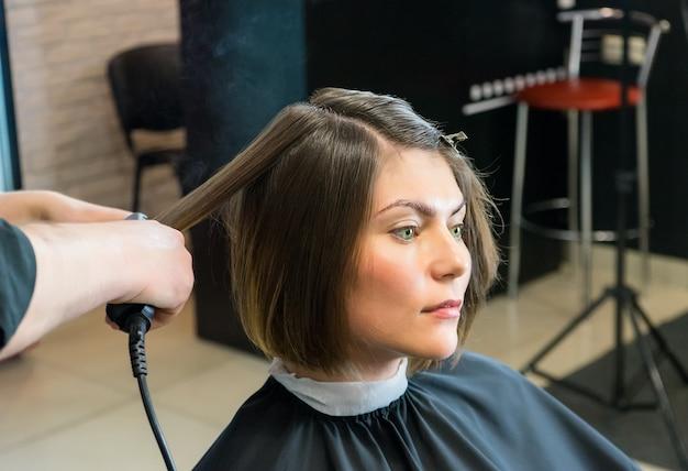 Friseur glättet die haare der hübschen frau im schönheitssalon.