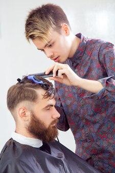 Friseur haare schneiden mit schere und kamm. seitenansicht des mannes im friseurladen...