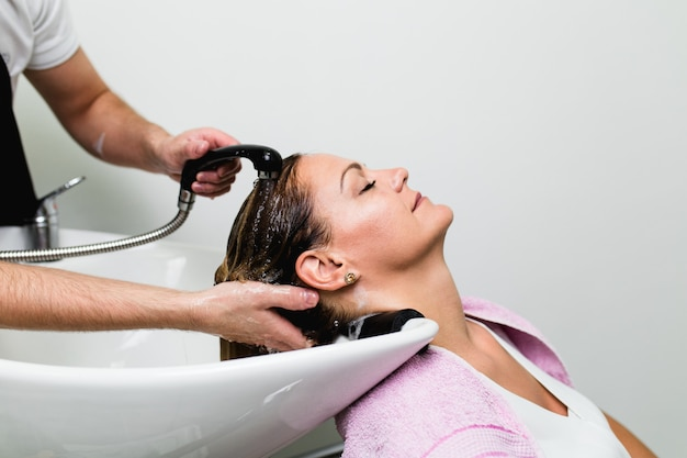 Friseur haare waschen einer schönen frau im friseursalon.