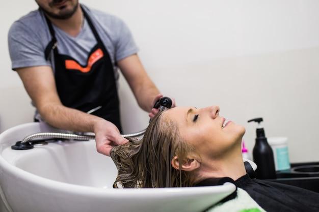 Friseur haare waschen einer schönen reifen frau im friseursalon.