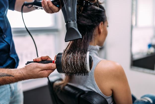 Friseur haartrockner mit föhn und rundbürste im friseursalon.