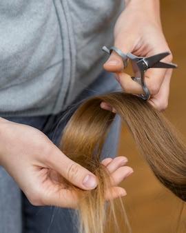 Friseur hält haarlocke und schere