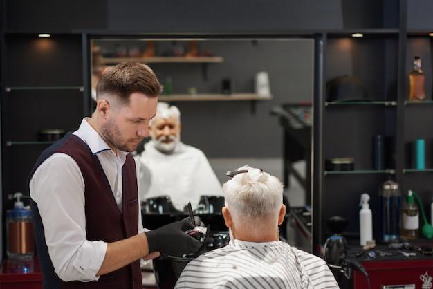 Friseur in den schwarzen handschuhen, die den haarschnitt des mannes trimmen.
