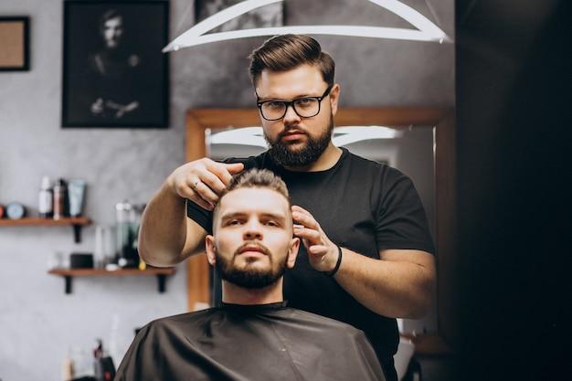 Friseur in einem friseurladen, der haare eines kunden stylt
