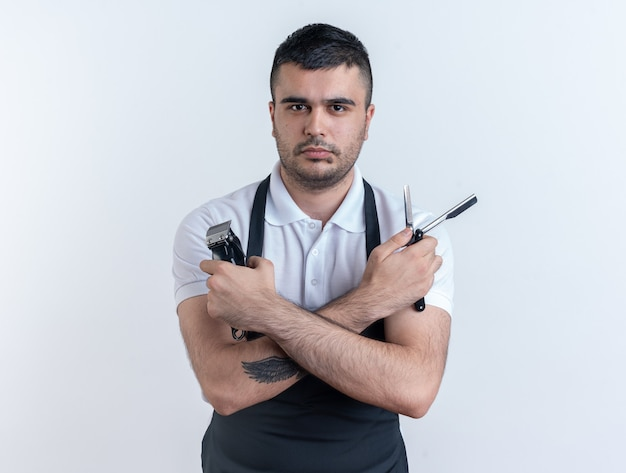 Friseur in schürze mit friseurwerkzeugen, die mit ernstem, selbstbewusstem ausdruck auf weißem hintergrund in die kamera schauen