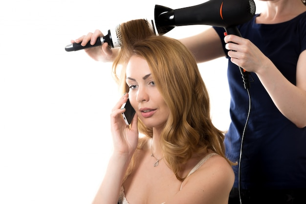 Friseur kämmen eine frau, während sie am telefon spricht