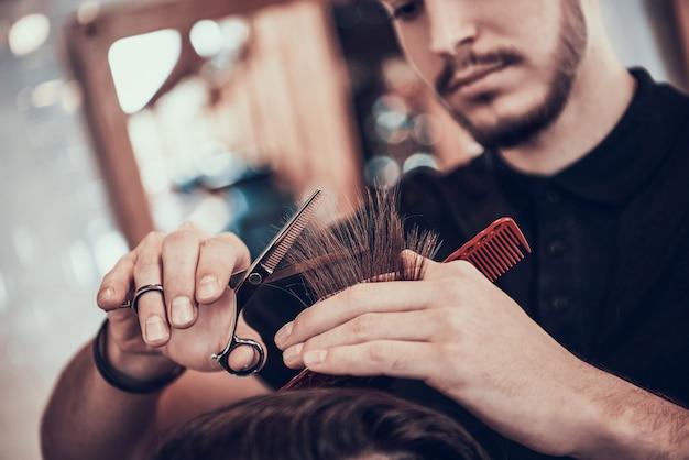 Friseur kämmt hübsches mannhaar mit händen.
