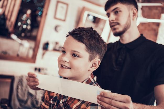 Friseur klebt childs nacken vor dem haarschneiden.