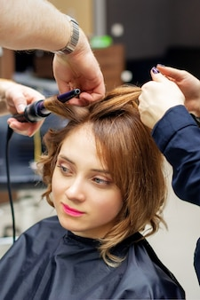 Friseur lockt langes hellbraunes haar