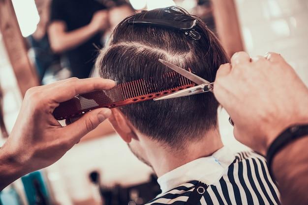 Friseur macht ein muster auf dem kopf des kunden blind.