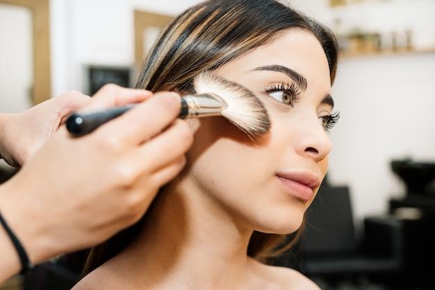 Friseur macht ein schönes kaukasisches mädchen mit langen haaren und großen grünen augen und sehr hübsch