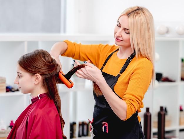 Friseur macht frisur für langes haar modell und wickelt locken mit einem haarbügeleisen