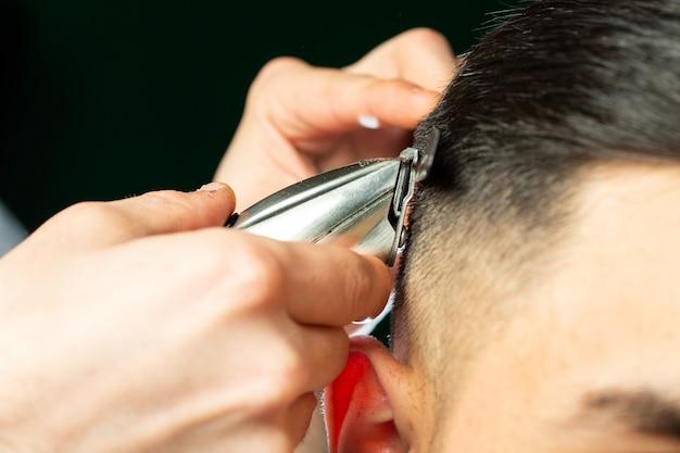 Friseur macht haarschnitt mit schneidemaschine