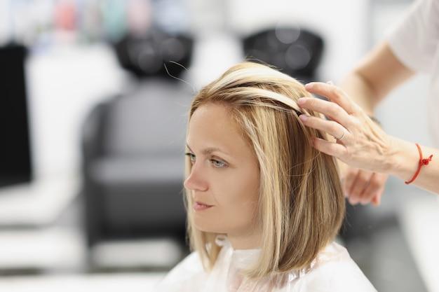 Friseur macht haarstyling für frauenkunden im schönheitssalon. haarpflegekonzept