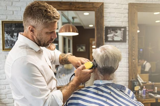Friseur macht stilvollen haarschnitt für einen gutaussehenden alten mann im friseursalon