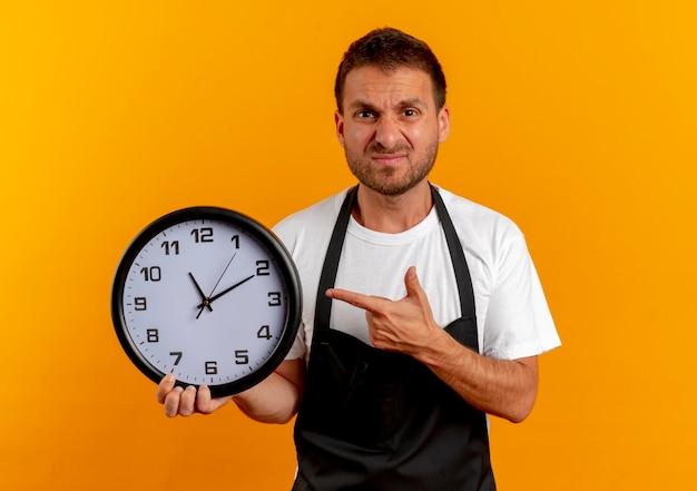 Friseur mann in der schürze hält wanduhr zeigt mit dem finger darauf und schaut nach vorne unzufrieden über orange wand stehen