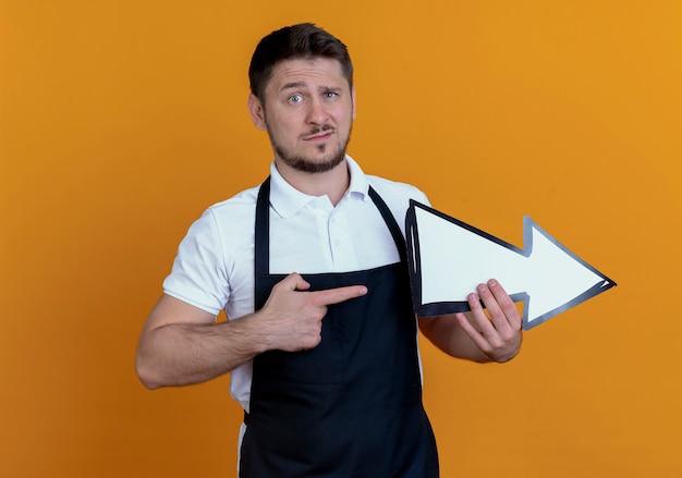Friseur mann in der schürze hält weißen pfeil mit dem finger darauf stehend über orange wand