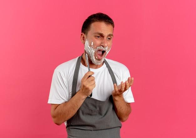 Friseur mann in der schürze mit rasierschaum auf seinem gesicht, das seinen bart unter verwendung des rasiermessers rasiert, das mit traurigem ausdruck auf gesicht steht, das über rosa wand steht