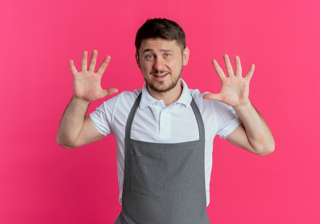 Friseur mann in der schürze zeigt und zeigt mit den fingern nummer zehn lächelnd über rosa wand stehend