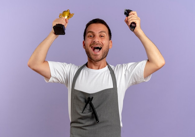 Friseur mann in schürze hält haarschneidemaschine und trophäe glücklich und aufgeregt freut sich über seinen erfolg über lila wand stehen