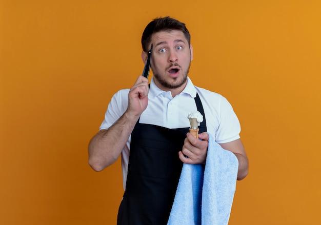 Friseur mann in schürze mit handtuch auf der hand hält rasierpinsel mit schaum und rasiermesser verwirrt vergessen etwas wichtiges über der orangefarbenen wand stehen